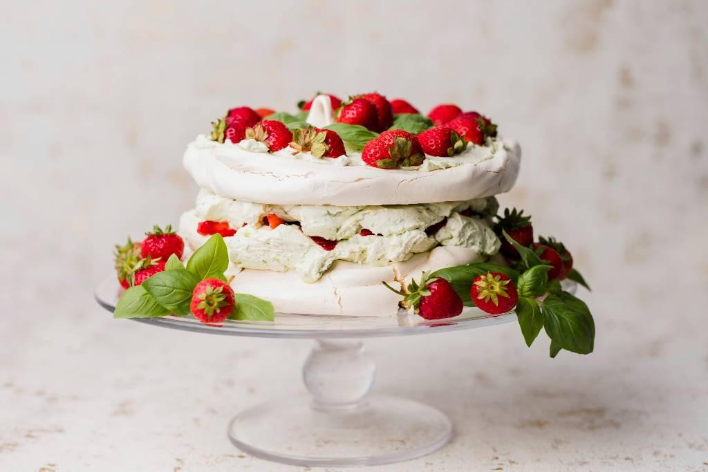 tort bezowy ze świeżymi owocami truskawek i listkami świeżej bazylii