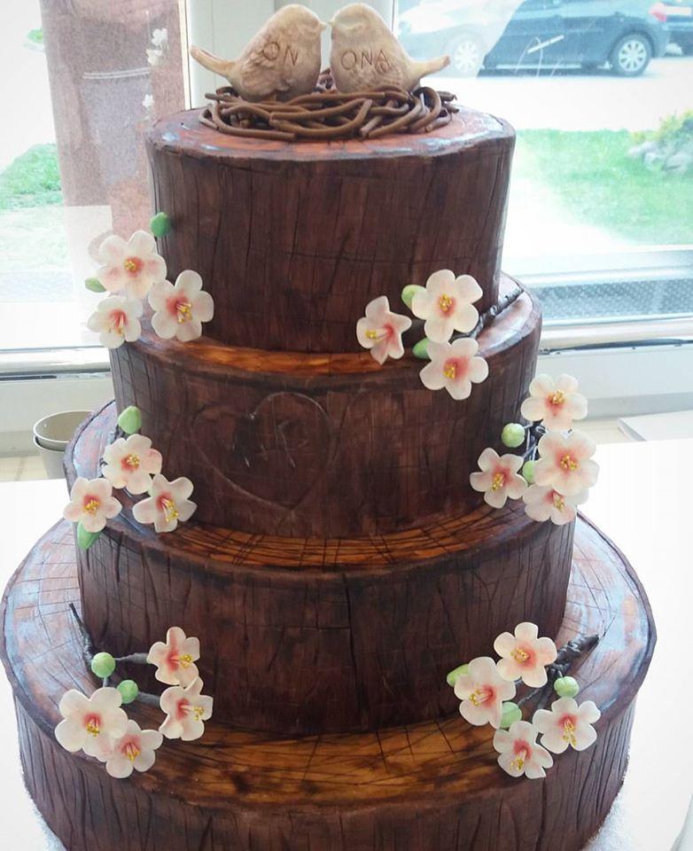 tort ślubny w kształcie pnia drzewa z kwiatami