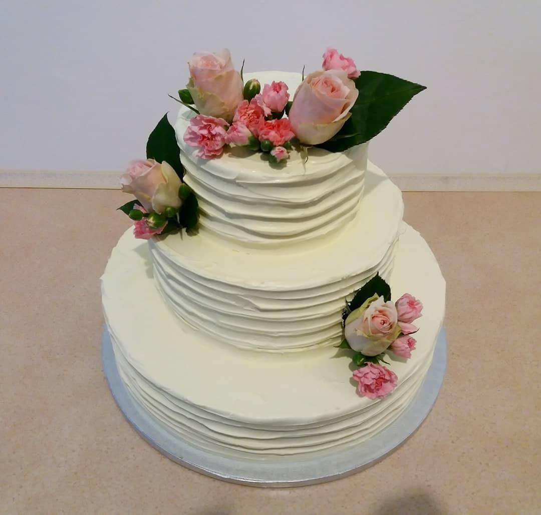 tort ślubny pokryty kremem z dekoracją ze świeżych róż